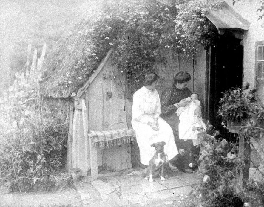 Avon Ford Cottage porch, Hampton Lucy. Two women, seated, with baby and dog.  1900s |  IMAGE LOCATION: (Warwickshire County Record Office)