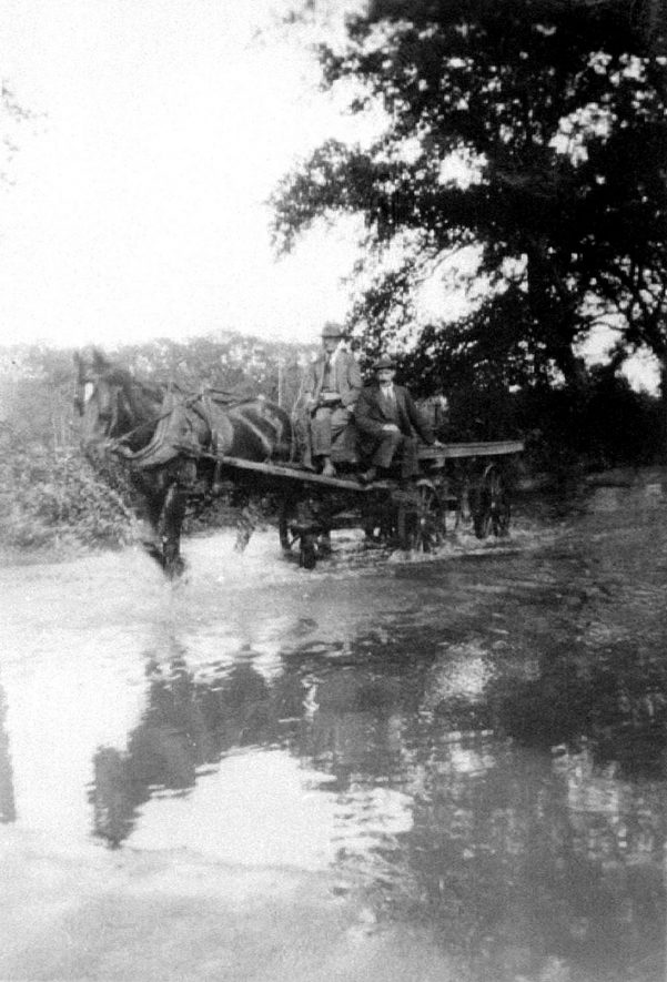 Horse and cart wading through flood water in Charlecote Road, Hampton Lucy.  1930s |  IMAGE LOCATION: (Warwickshire County Record Office)