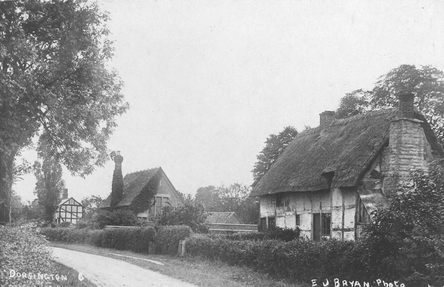 Part of street, showing two thatched, timber-frame cottages, Dorsington.  1900s |  IMAGE LOCATION: (Warwickshire County Record Office)