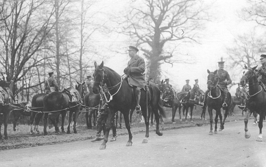 Cavalry assembled on road outside village. King George V inspecting troops from horseback. 1910s.