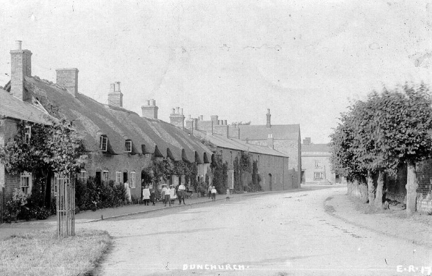 Street in Dunchurch with row of thatched cottages and group of children.  1900s [This row of cottages still remain today and are pretty much unchanged. They are situated on the Southam road with the site of Dunchurch Hall opposite which is now a small housing development] |  IMAGE LOCATION: (Warwickshire County Record Office)