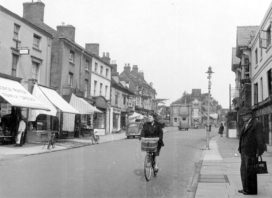 The Square, Kenilworth.  Shops, pedestrians and woman on bicycle.  1947 |  IMAGE LOCATION: (Warwickshire County Record Office)
