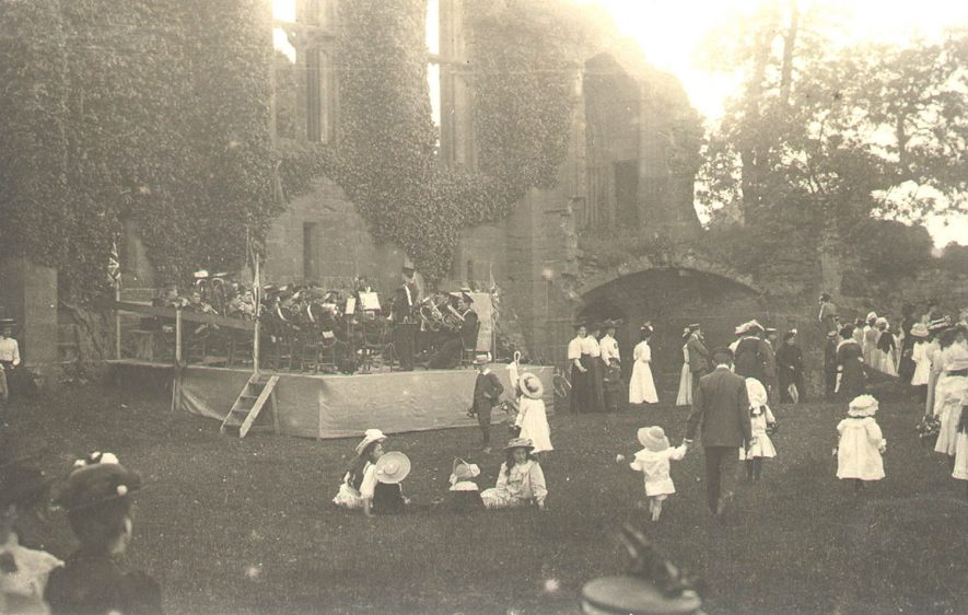 Band playing at Kenilworth Castle, watched by a crowd of adults and children.  1900s |  IMAGE LOCATION: (Warwickshire County Record Office)