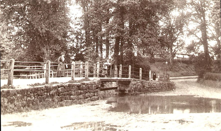 The ford, with a lady and two children on the footbridge, Castle Road, Kenilworth.  1910s |  IMAGE LOCATION: (Warwickshire County Record Office)