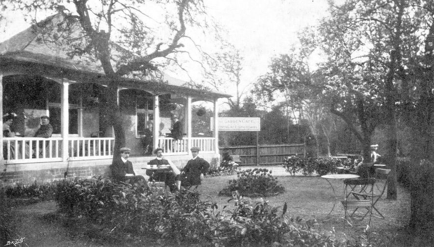 The exterior of The Garden Cafe, Kenilworth, with people sitting at tables in the garden.  1900s |  IMAGE LOCATION: (Warwickshire County Record Office)