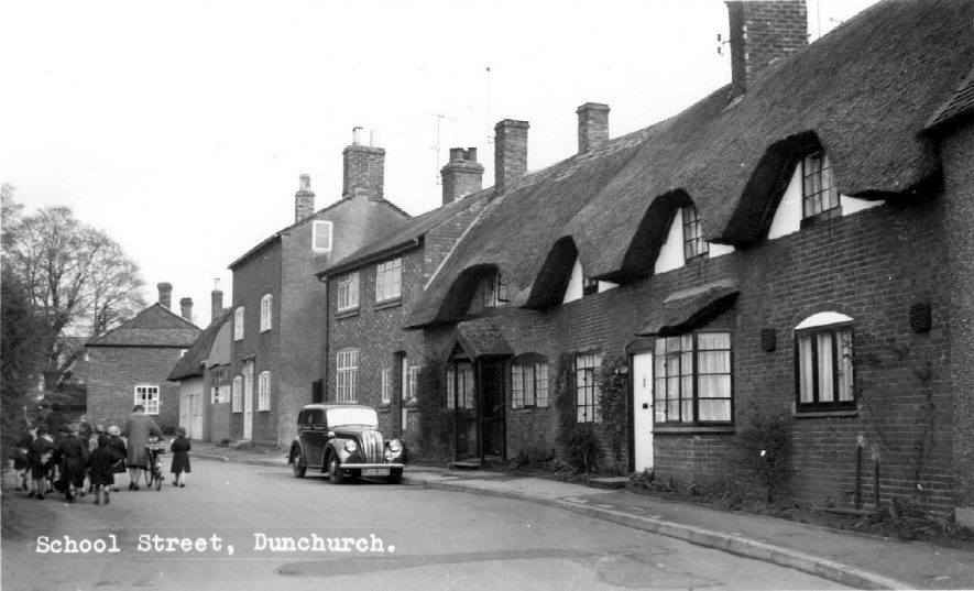 School Street, Dunchurch, showing old thatched cottages with car and children in front.  1950s |  IMAGE LOCATION: (Warwickshire County Record Office)