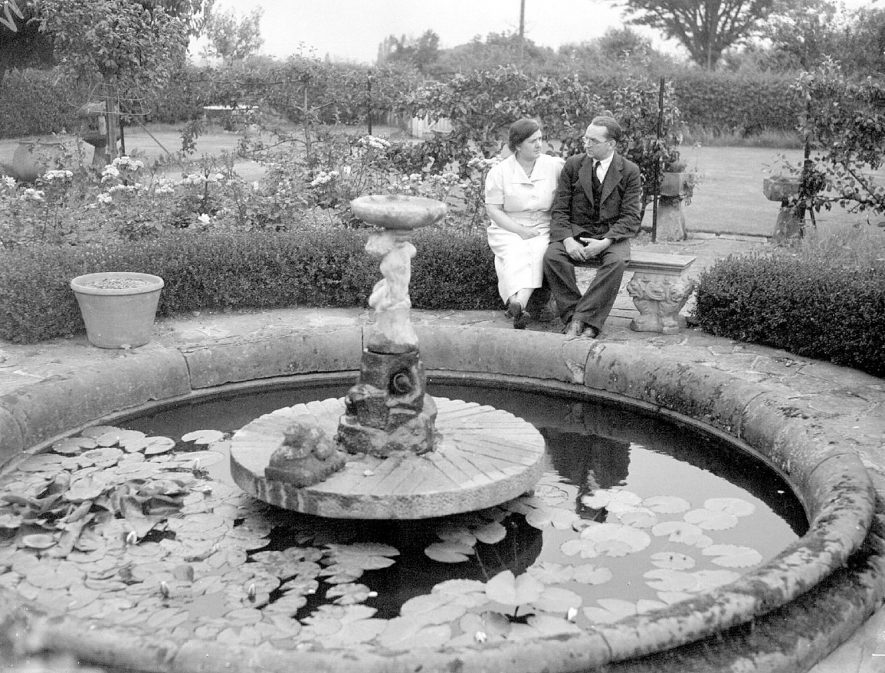 Lady and gentleman sitting beside a pond in the gardens at Rudfyn (now Redfern) Manor, Chase Lane, Kenilworth.  July 17th 1940 |  IMAGE LOCATION: (Warwickshire County Record Office)
