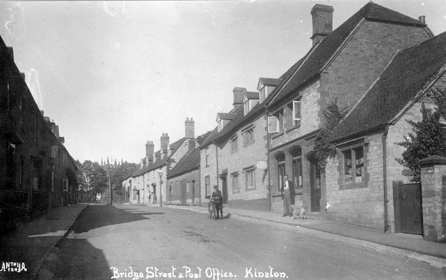 Bridge Street, Kineton, showing post office and cottages.  Man with bicycle.  1920s |  IMAGE LOCATION: (Warwickshire County Record Office)