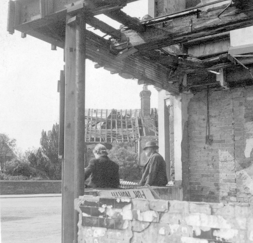 Bomb damage in The Square, Kenilworth. Man and woman seated.  1947 |  IMAGE LOCATION: (Warwickshire County Record Office)