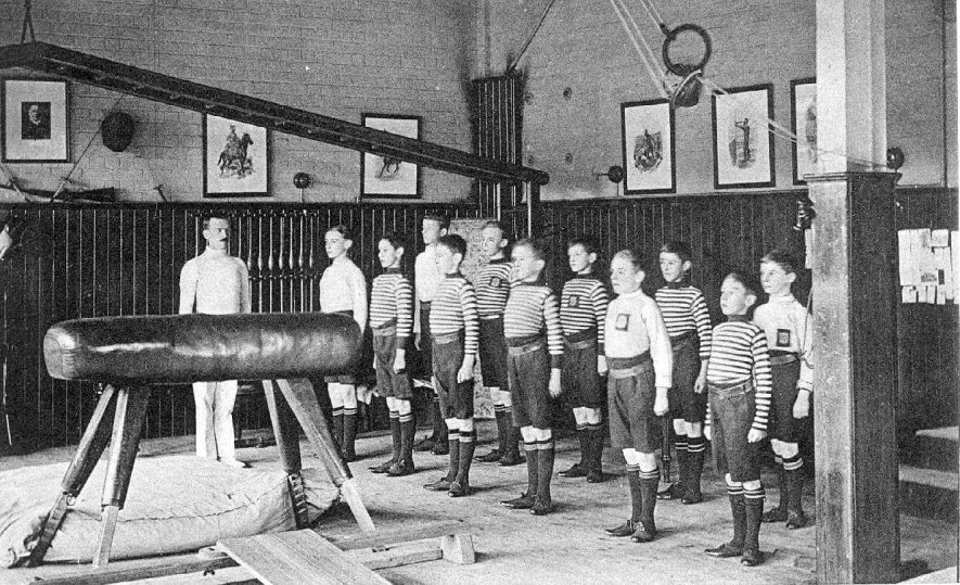 Group of boy gymnasts and instructor in the gymnasium in Dunchurch Hall prep school.  1900s |  IMAGE LOCATION: (Warwickshire County Record Office)