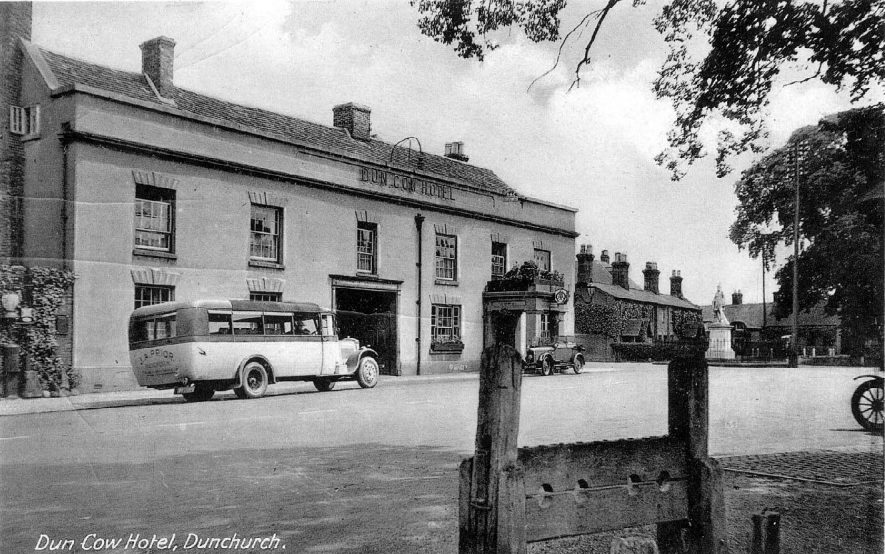 The Dun Cow Hotel in the centre of Dunchurch with a motor car and bus standing outside. Statue in the background and stocks in the foreground.  1910s |  IMAGE LOCATION: (Warwickshire County Record Office)