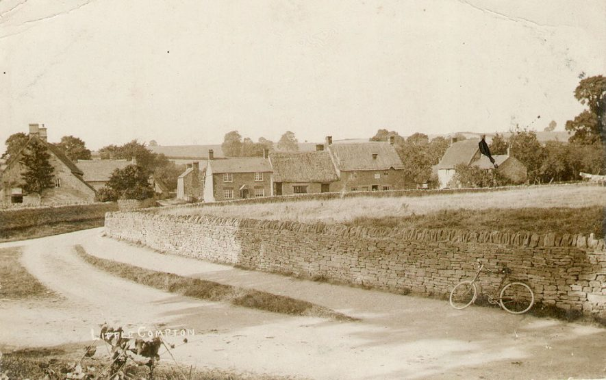 A view of Little Compton, with cottages in the background and a bicycle leaning against a wall in the foreground.  1900s |  IMAGE LOCATION: (Warwickshire County Record Office)