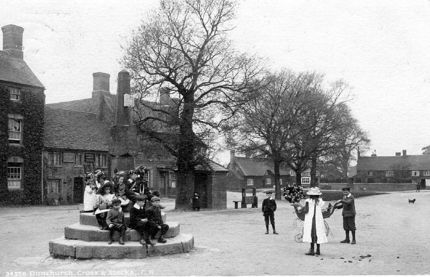 The square, with broken Cross and stocks, Dunchurch. Children sitting on steps of Cross with garlands.  1900s |  IMAGE LOCATION: (Warwickshire County Record Office)