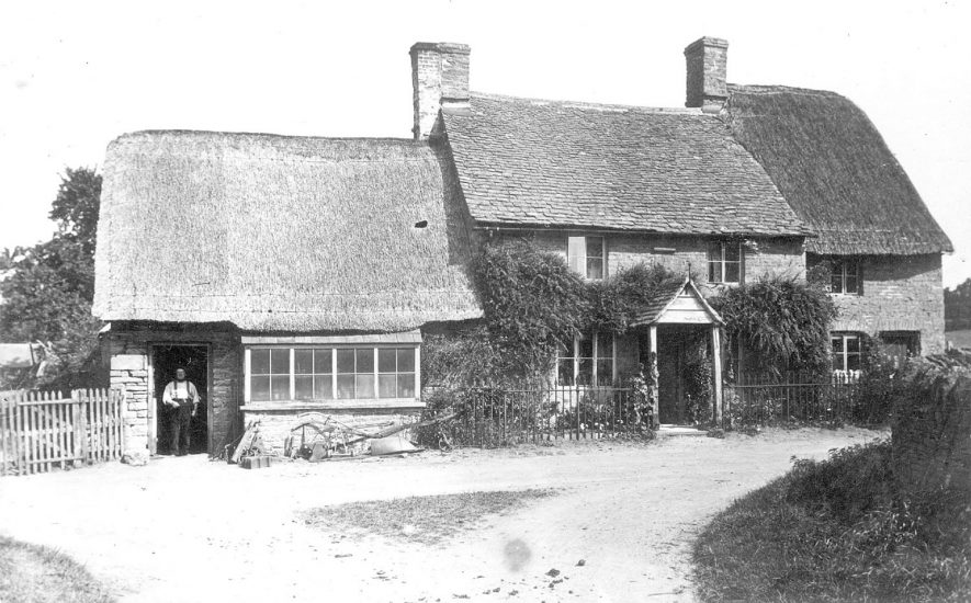The blacksmiths shop and adjoining cottages, Little Compton. A plough share is standing in front of the smithy.  1900s |  IMAGE LOCATION: (Warwickshire County Record Office)