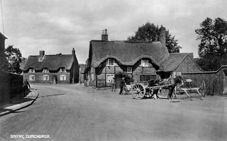 The smithy, thatched and timbered cottages, horse and cart and agricultural hay rake, Dunchurch.  1920s |  IMAGE LOCATION: (Warwickshire County Record Office)