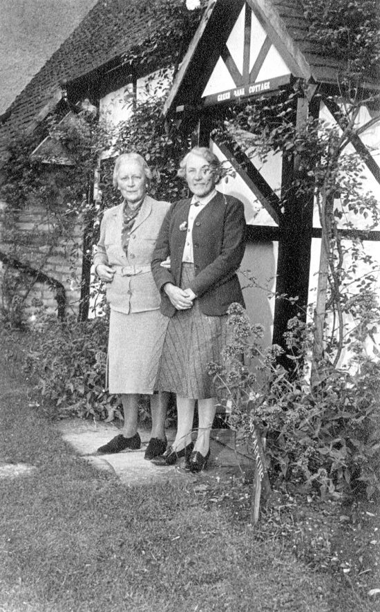 Miss Emily Cooper (from Toronto, Canada) and Mrs Mackintosh standing at the entrance to Greenbank Cottage, Welford on Avon.  1947 |  IMAGE LOCATION: (Warwickshire County Record Office) PEOPLE IN PHOTO: Mackintosh, Mrs, Mackintosh as a surname, Cooper, Miss Emily, Cooper as a surname