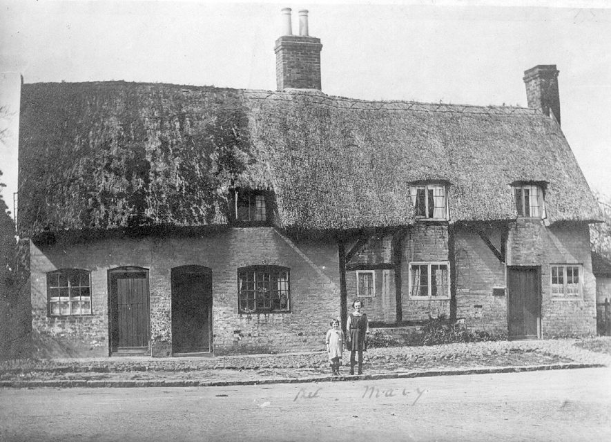 Two cottages on The Green at Monks Kirby, with two girls standing outside.  1925 |  IMAGE LOCATION: (Warwickshire County Record Office)