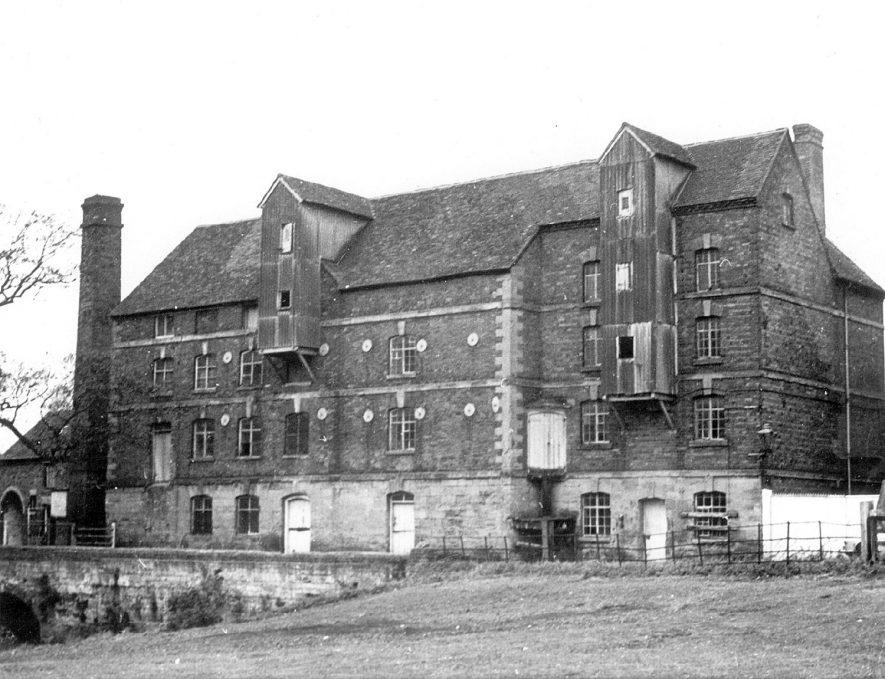 Front view of Rock mills, Milverton. The mill buildings span the river - its early source of power. The chimney to the left was erected in connection with diesel power. In the left hand corner are the outbuildings and stables. Moving from left to right we see the first section and original part of the building. To the extreme right is the building which was added in 1797.   1971 |  IMAGE LOCATION: (Warwickshire County Record Office)