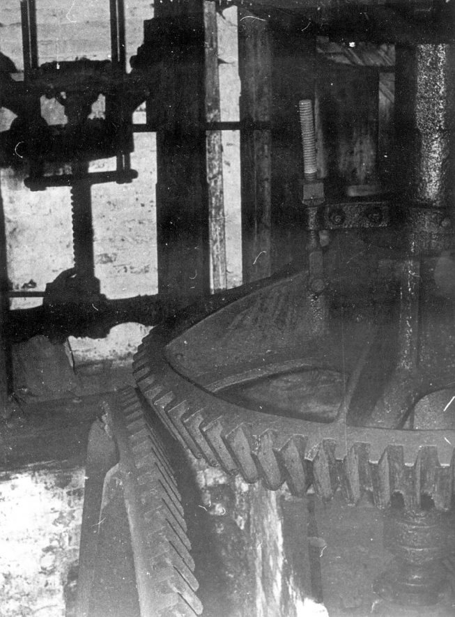 Rock mills, Milverton. This photograph shows the main hoist. It is possible to discern the canvas belt which rises from the floor below, encircles the large wheel and descends again. This supplied the power to turn the wheel and the shaft which projects from it. The hoist chain can be seen wrapped around the shaft. Notice how worn the beam is in the foreground where for years chains have been wrapped around it.  1971 |  IMAGE LOCATION: (Warwickshire County Record Office)