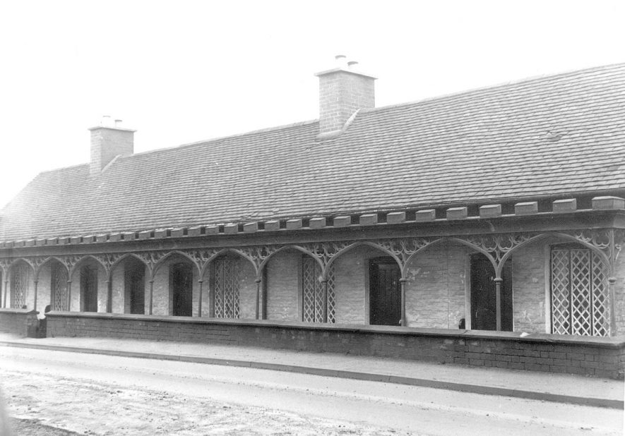 Row of almshouses in Mancetter built in the 19th century with cast iron arches in front.  December 1968 |  IMAGE LOCATION: (Warwickshire County Record Office)