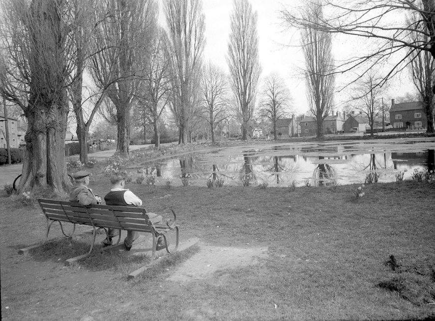 Long Itchington village pond, with two men sitting on a seat.  April 24th 1956 |  IMAGE LOCATION: (Warwickshire County Record Office)