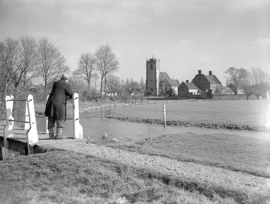 Holy Trinity church and River Itchen, Long Itchington. A man is standing on the footbridge looking towards the church.  February 26th 1953 |  IMAGE LOCATION: (Warwickshire County Record Office)