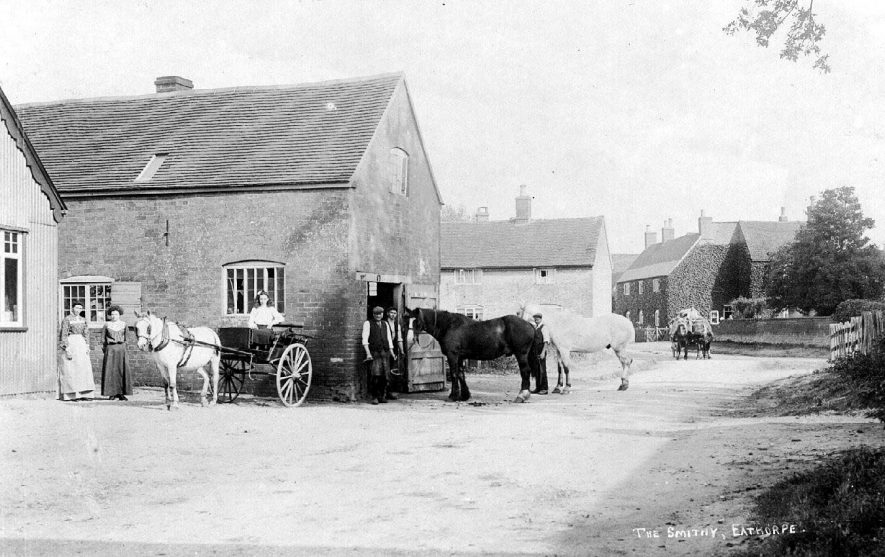 The Smithy at Eathorpe with horses and workers at door. Also a pony and trap with three ladies.  1900s |  IMAGE LOCATION: (Warwickshire County Record Office)