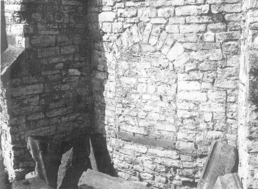 Part of wall from unidentified ruined stone building, showing filled in window arch, Newbold on Stour.  1920s [It is very likely that this photo relates to the back of Hands Farm, where there was and still are the remains of a bread oven. The bread oven still remained in 1996 and could become functional again.The bread oven room was later used as a coalhouseand and there was a dairy next to the bread oven.On the side of the front wall is a stone set into the brickwork with the date 1699. Three Grand National winners came from the Hands stable and it is said that their beer and cider was renowned throughout the country.] |  IMAGE LOCATION: (Warwickshire County Record Office)