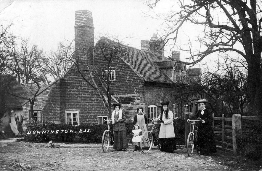 Ladies with bicycles and child standing outside cottages in Dunnington.  1900s |  IMAGE LOCATION: (Warwickshire County Record Office)