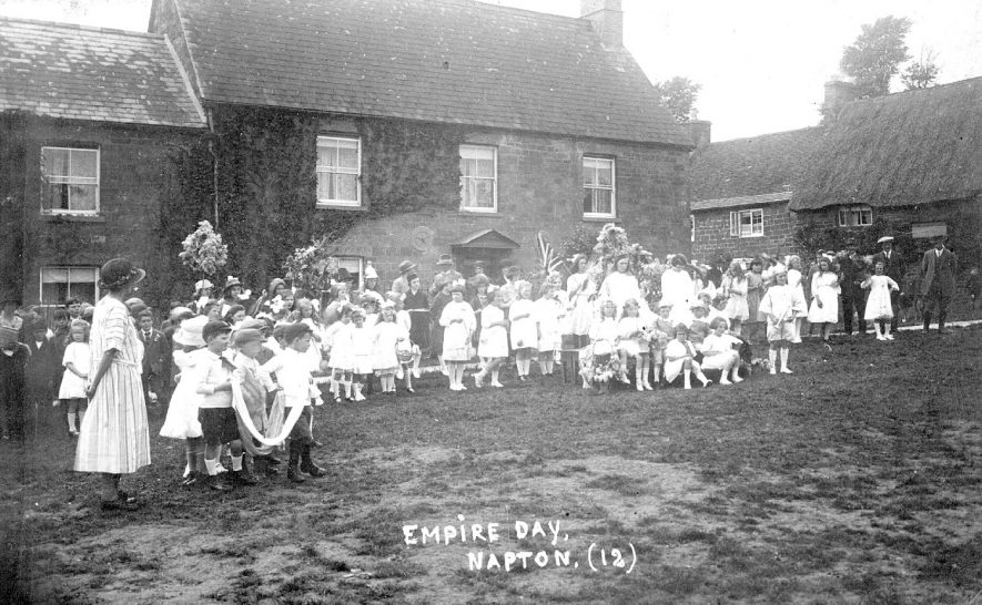 Group of children dressed up to celebrate Empire Day, watched by adults. Napton on the Hill.  1920s |  IMAGE LOCATION: (Warwickshire County Record Office)