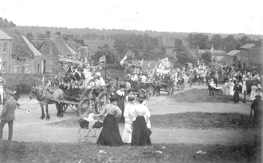 Coronation celebrations in High Street, Napton on the Hill. A parade of decorated  horse drawn carts and a mock coronation coach are filled with children, adults, flags and banners. Groups of people are watching the parade pass.  1911 |  IMAGE LOCATION: (Warwickshire County Record Office)