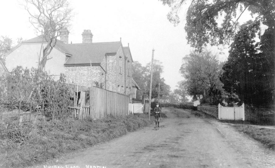 Cottages in Vicarage Road, Napton on the Hill.  1900s  [View looking along Vicarage Road. White gates on the right is the entrance to the former Vicarage, now demolished.] |  IMAGE LOCATION: (Warwickshire County Record Office)