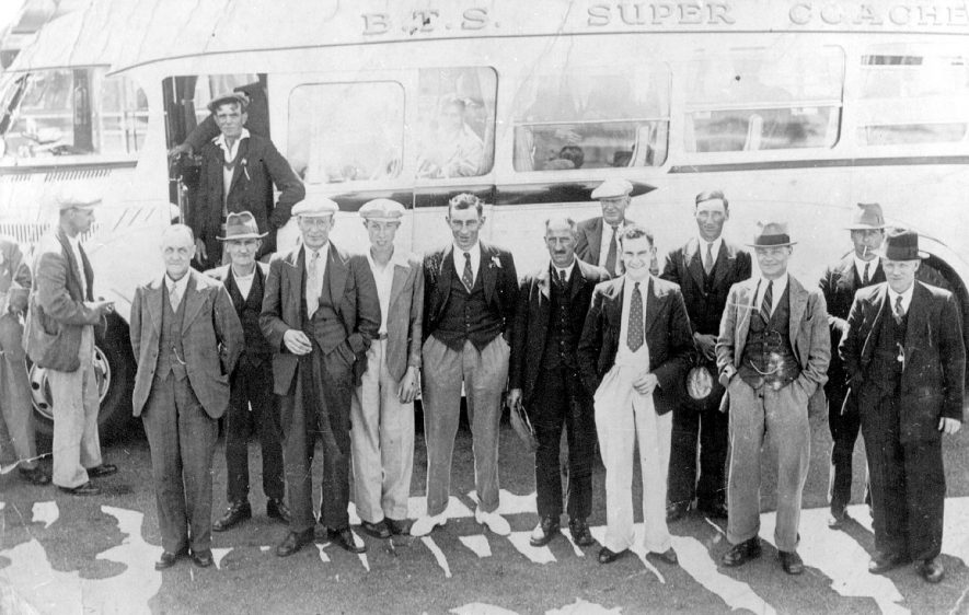 B.T.S. Super Coach with a group of men standing in front, possibly going on a works outing. Napton on the Hill.  1920s |  IMAGE LOCATION: (Warwickshire County Record Office)