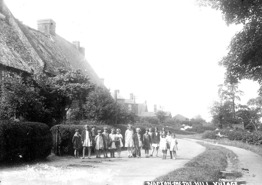 Lane with cottages and a line of children standing in road, Napton on the Hill.  1920s [This view is looking along Vicarage Road] [The children are outside what is known as