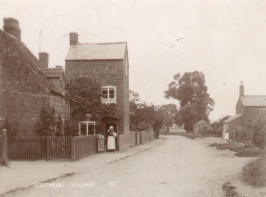 Cottages in Northend. A lady is standing in the gateway of one of the cottages.  1900s |  IMAGE LOCATION: (Warwickshire County Record Office)