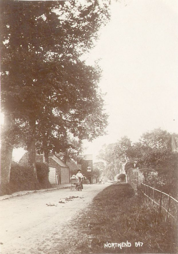 A lady wheeling a perambulator along a lane in Northend.  1900s |  IMAGE LOCATION: (Warwickshire County Record Office)