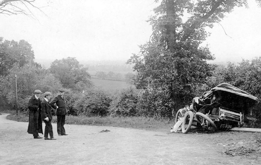 Scene of a motor car accident on Sunrising Hill, Edgehill, which happened on June 10th 1907. Three men looking at wrecked car.    IMAGE LOCATION: (Warwickshire County Record Office)