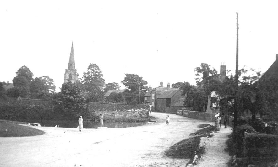 Looking along a road in Newton Regis, with the church in the background.  1950s |  IMAGE LOCATION: (Warwickshire County Record Office)