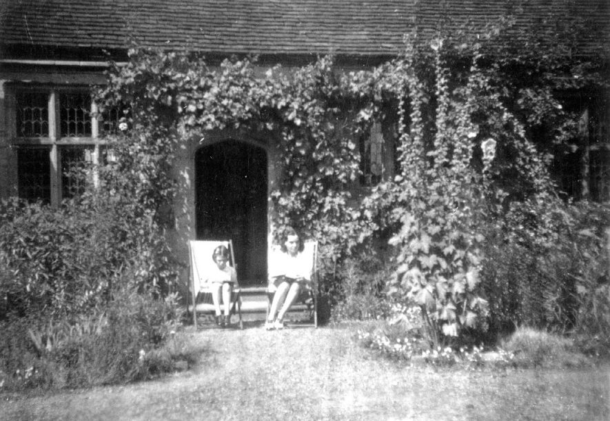 Part of the Priory building, Priory Park, Warwick.  Doorway and two girls sitting outside in garden. Most of the Priory had already been demolished and removed to the US.  1940s |  IMAGE LOCATION: (Warwickshire County Record Office)