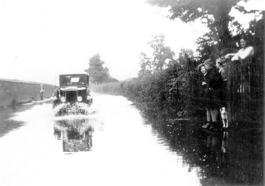 Car driving along flooded Hampton Road, Warwick, watched by the Potter family of Old Kennels Farm.  1930s |  IMAGE LOCATION: (Warwickshire County Record Office) PEOPLE IN PHOTO: Potter, as a surname