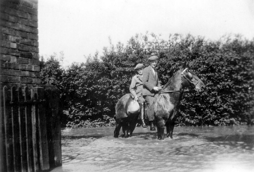 Bob Potter (boy) of Old Kennels Farm, Hampton Road, Warwick, and Alf Newman on Weaver Alf's horse on flooded roadway.  1930s |  IMAGE LOCATION: (Warwickshire County Record Office) PEOPLE IN PHOTO: Potter, Bob, Potter, as a surname, Newman, Alf, Newman as a surname