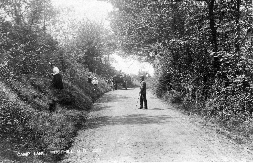Camp Lane, Edgehill with people on steep banks on sides of road, possibly collecting blackberries or wild flowers.  1900s |  IMAGE LOCATION: (Warwickshire County Record Office)