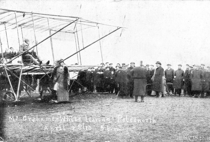 Mr Graham White about to take off in a bi-plane with a lady and a crowd of men watching, Polesworth.  28th August 1910 |  IMAGE LOCATION: (Warwickshire County Record Office)