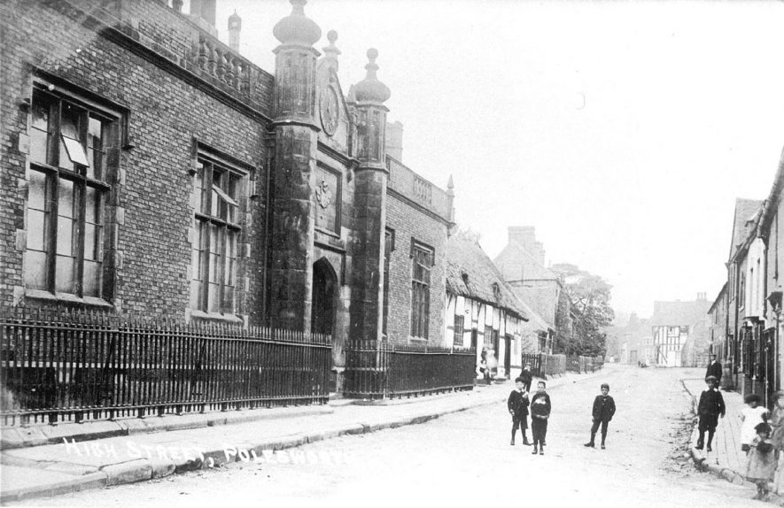 Group of children in High Street, Polesworth. The large building on the left is the Nethersole Centre, formerly the Junior School until the 1970s.  1900s |  IMAGE LOCATION: (Warwickshire County Record Office)
