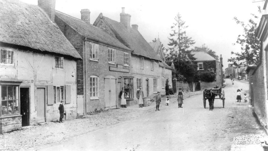Shops and cottages in Lutterworth Road, Pailton. A group of people and a horse and cart are standing in the road.  Circa 1900 |  IMAGE LOCATION: (Warwickshire County Record Office)