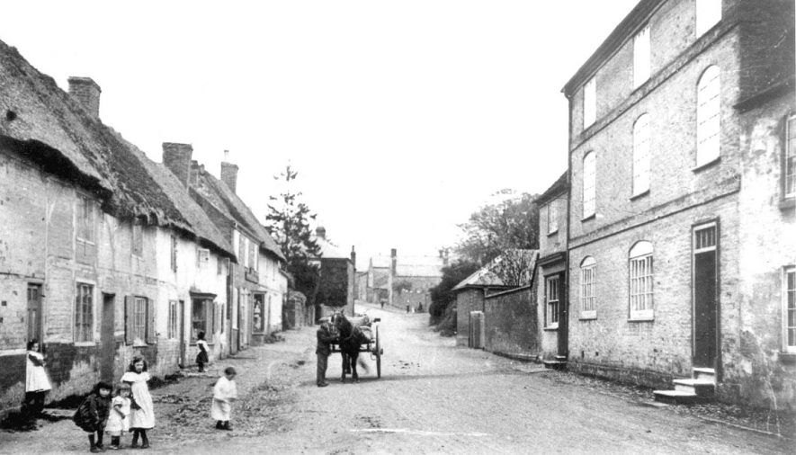 Cottages in Lutterworth Road, Pailton. Children and a horse and cart are standing in the road.  Circa 1900 |  IMAGE LOCATION: (Warwickshire County Record Office)