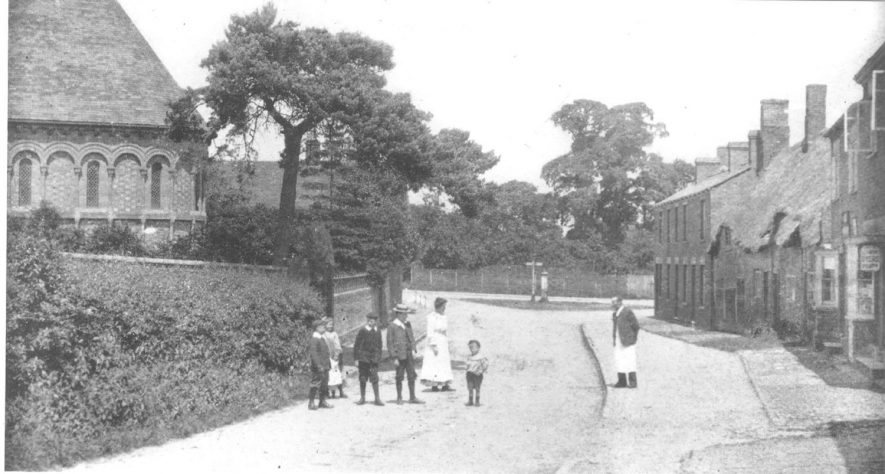 Group of children and adults standing at the bottom of Rugby Road, Pailton. The rear end of St Denys's church can also be seen.  Circa 1900 |  IMAGE LOCATION: (Warwickshire County Record Office)
