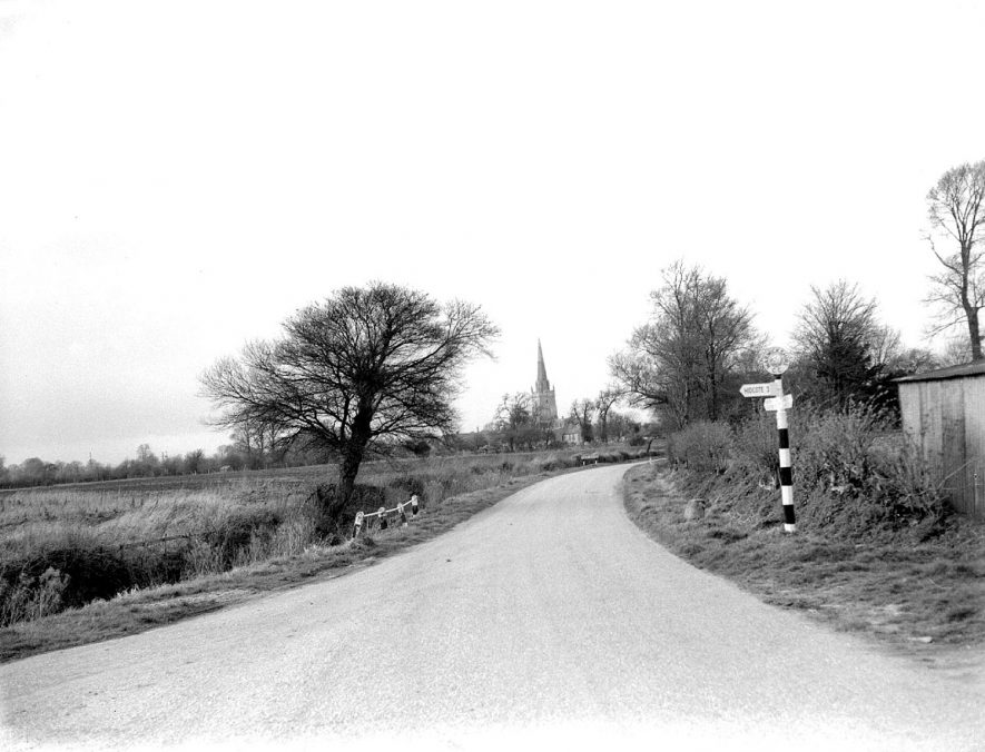 Road into Lower Quinton.  In the distance the parish church (St Swithin's).  1957 |  IMAGE LOCATION: (Warwickshire County Record Office)