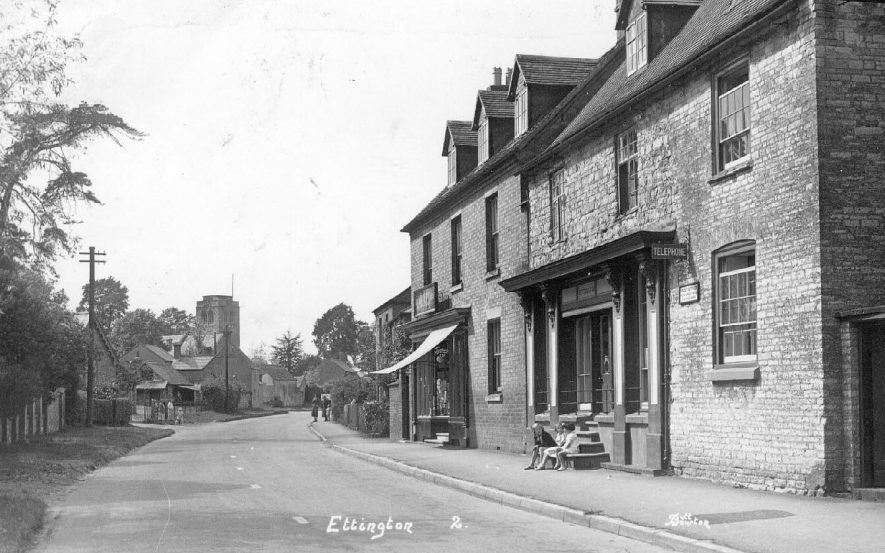A scene of the main street showing the church in the distance and some children sitting on the steps of the post-office, Ettington.  1930s |  IMAGE LOCATION: (Warwickshire County Record Office)