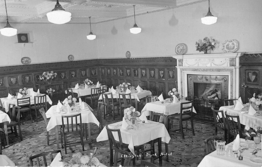 Interior of dining room of the Ettington Park Hotel, the tables set for a meal.  1940s |  IMAGE LOCATION: (Warwickshire County Record Office)